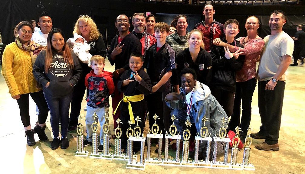 Competitors, family, and Master Anne posing in front of trophies.
